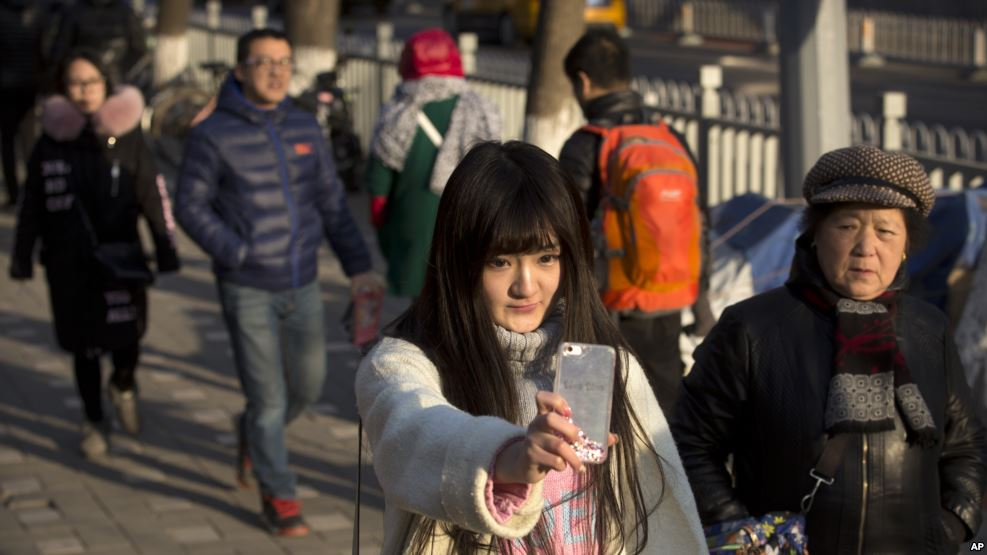 a woman holding a phone to face herself on a street in china