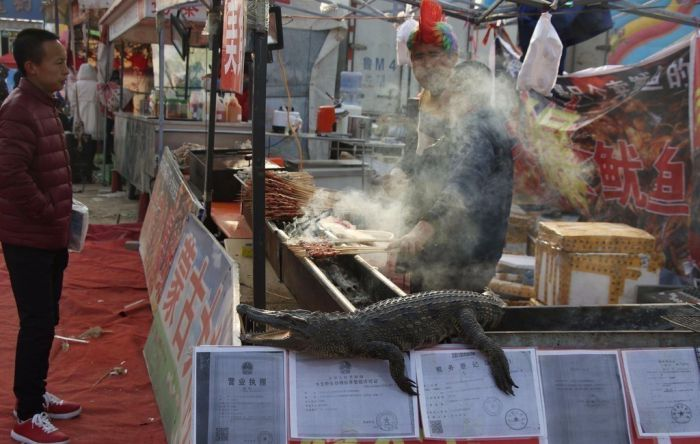 a vendor cooking crocodile meat in china