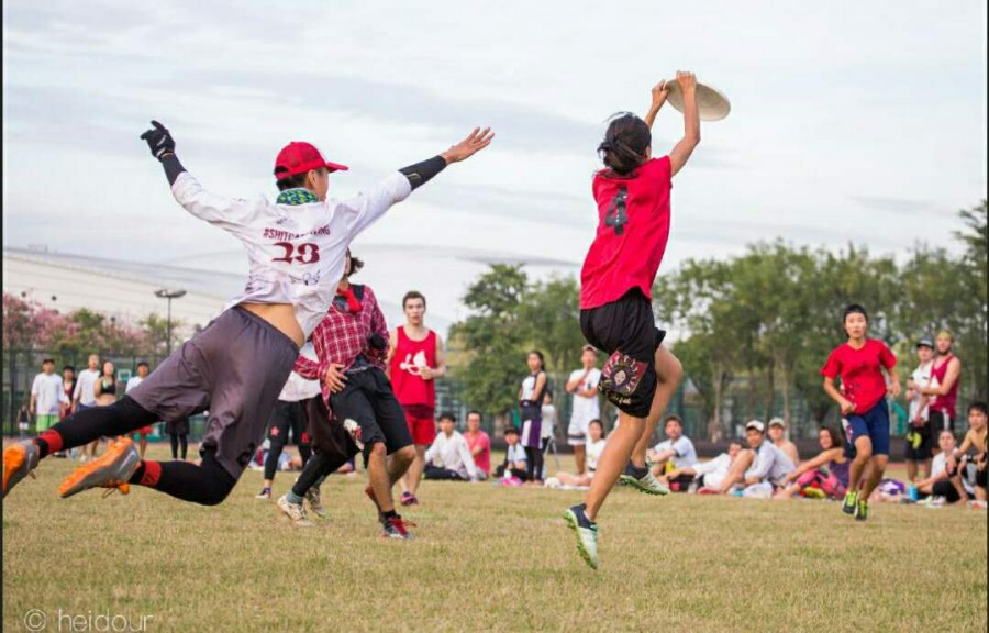 Players Reach for Frisbee in Game of Ultimate Frisbee