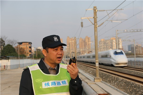 a safety officer on a radio next to a train track in china