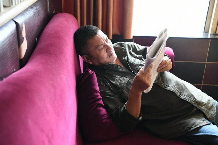 side view of a man lying on the sofa reading