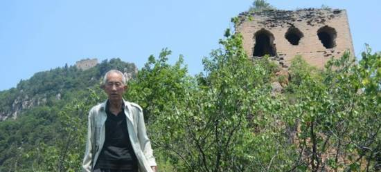 an old man in the trees in front of a tower at the great wall