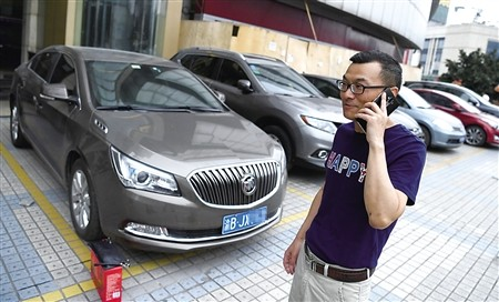 a man on his phone next to a row of cars