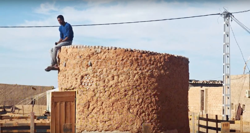 a man sitting on a home constructed using plastic bottles in algeria