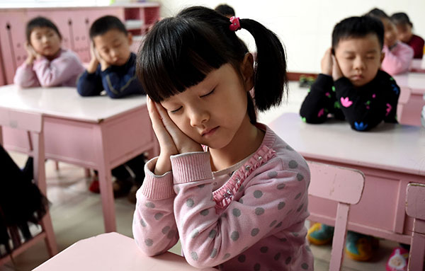 kids in a classroom pretending to sleep in china