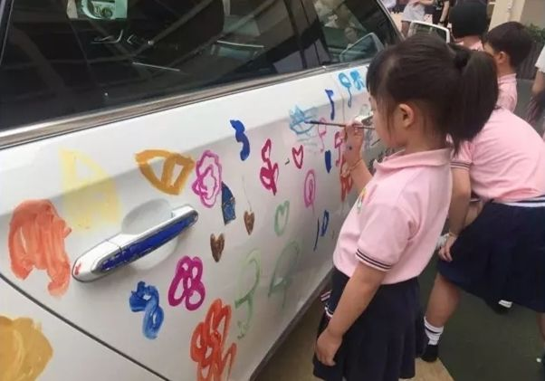 side view of a child painting on a car in china