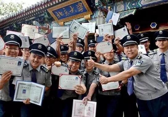 group of security guards from peking university holding their degree certificates