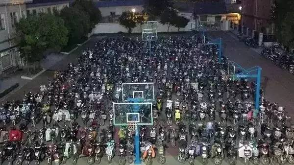 a lot of bikes parked in a playground at a school in china