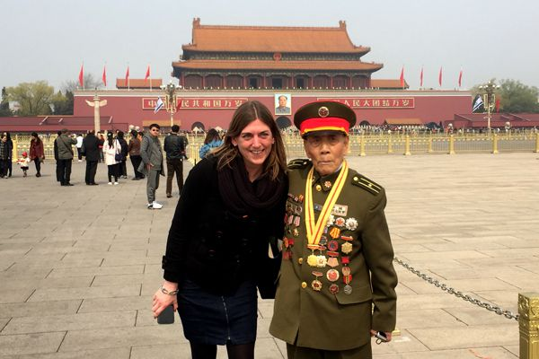 old veteran taking a photo with a tourist at tiananmen square in beijing