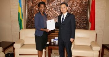 two officials from china and rwanda posing or a photo