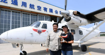 chinese couple posing for a photo next to an airplane