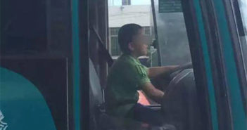 side view of a boy driving a bus in guangzhou