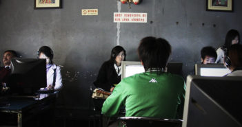 Chinese man playing games in internet cafe