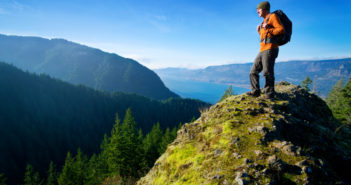 British man who visited 201 countries stands on rock overlooking scenery
