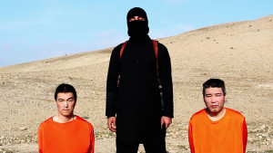 Two Japanese hostages kneel alongside their Islamic State captor