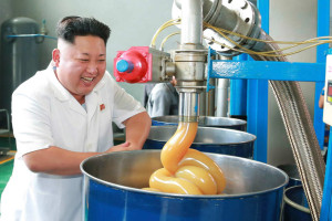 North Korean leader smiling as he inspects factory
