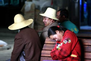 girl sleeping on a bench next to two men in hats talking