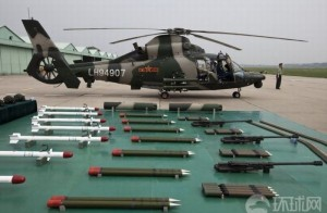 side view helicopter behind an array of weapons