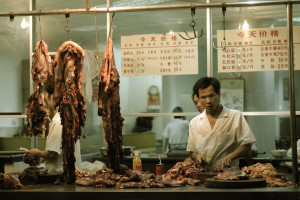 chinese butcher with meat laid out cutting