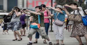 chinese tourists stoop down to take photos