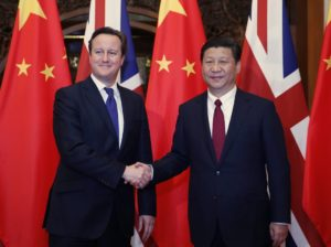 China's President Xi Jinping shakes hands with Britain's Prime Minister David Cameron in front of Chinese and British flags