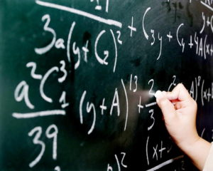 side view hand writes maths equation on chalk board