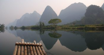 Traveling by boat along China river with mountains