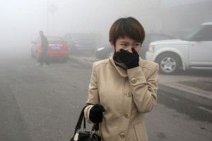 woman uses hand to cover face in high pollution enviroment