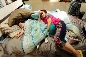 woman and child sleeping on IKEA showroom bed