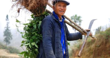 Chinese farmer carrying farming equipment