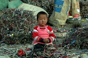 chinese child sitting among e-waste