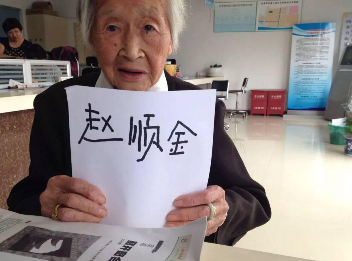 grandma zhou holding a pice of paper with her name written on it