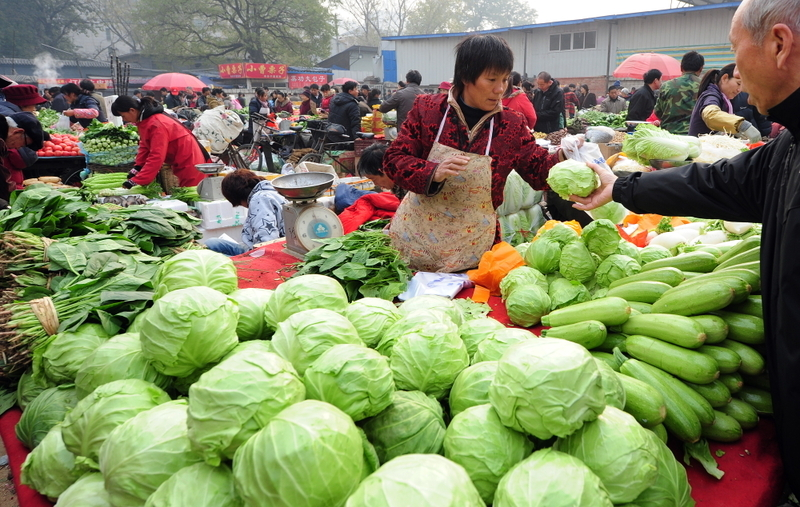 man buying vegetables from a woman at a beijing farmer's market