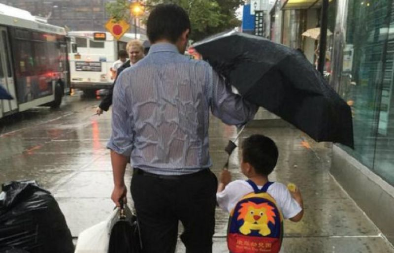 father shielding his son with umbrella in the rain