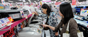 chinese tourists looking at appliances in shop in japan