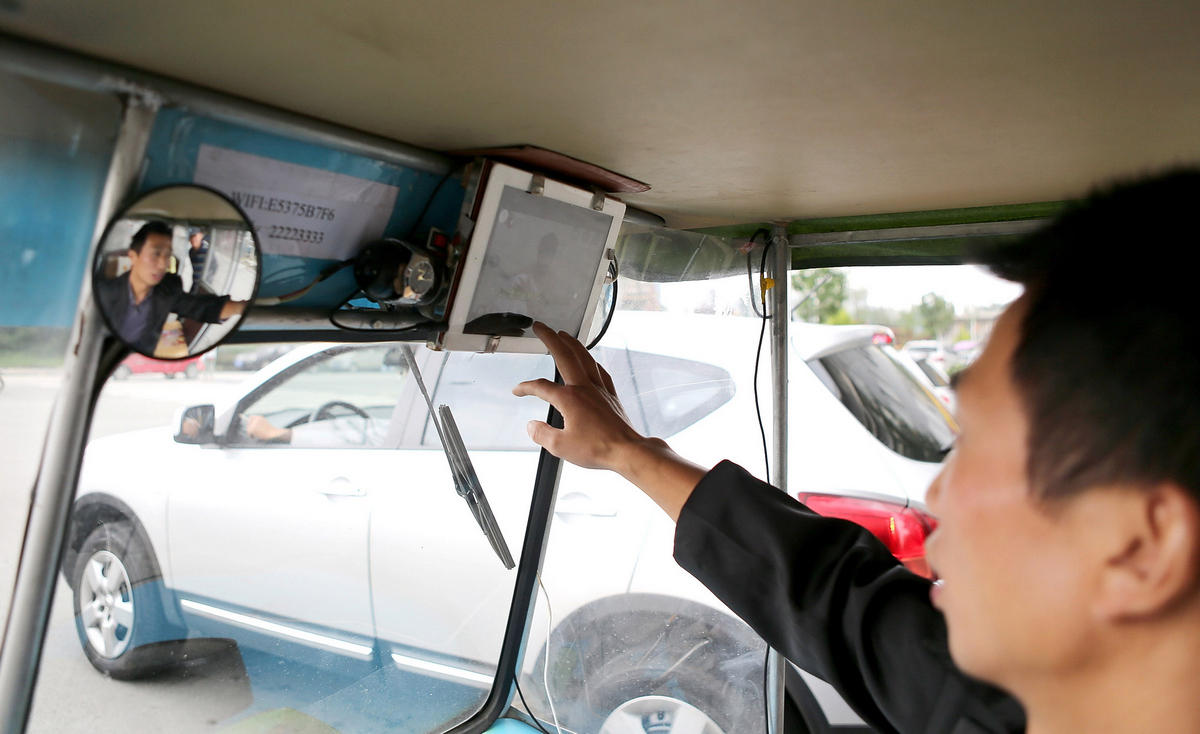 driver playing with iPad in his tricycle cab