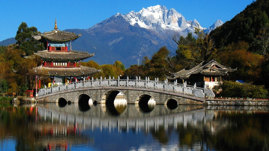 a picturesque view of bridge and mountains in lijiang