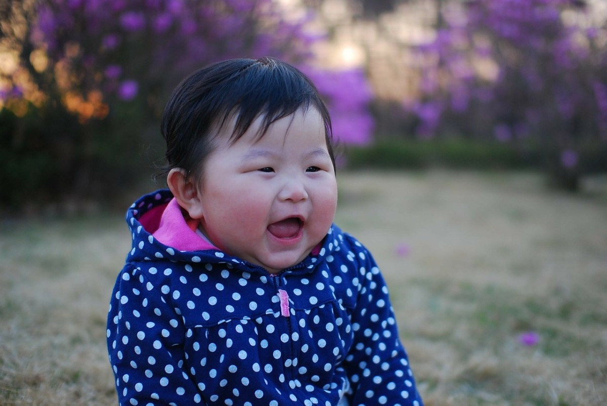 front view of baby sitting in a park smiling
