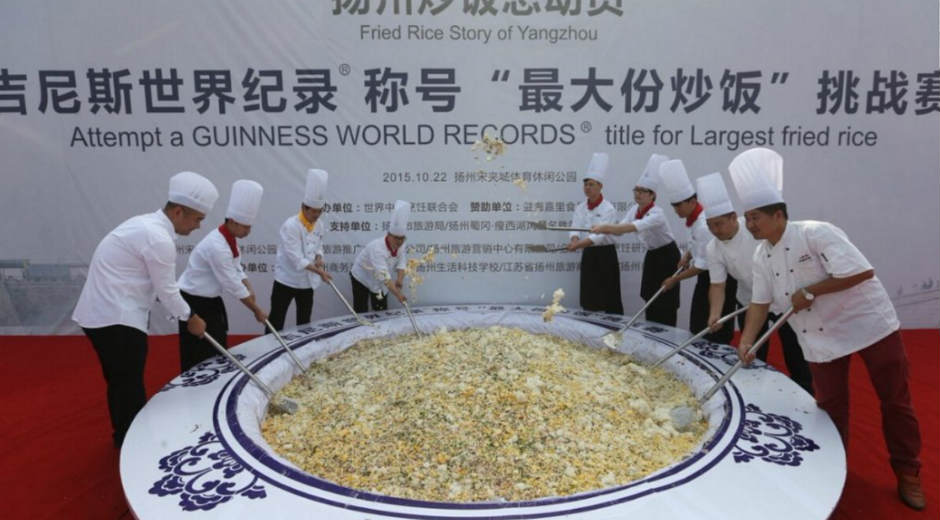 chinese chefs cooking fried rice in a huge bowl for a world record attempt
