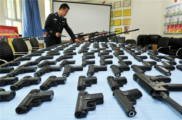 policeman inspects table full of seized guns in china