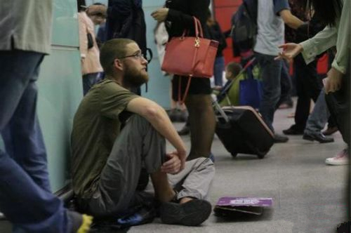 side view of foreign backpacker sitting on the floor of guangzhou station