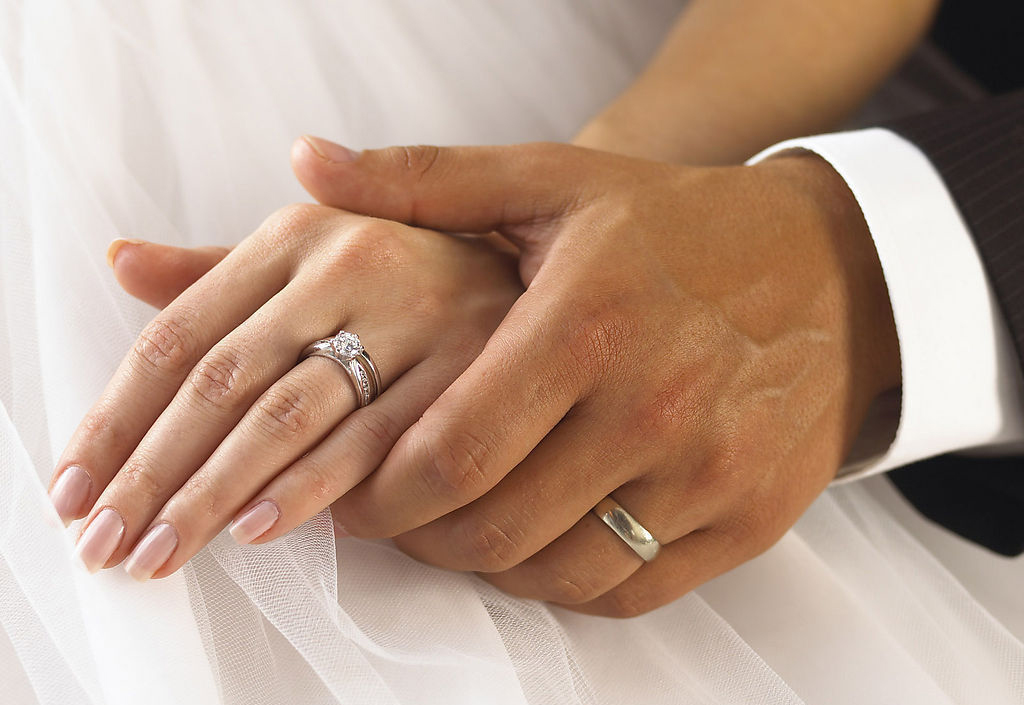 side view of two hands with wedding rings