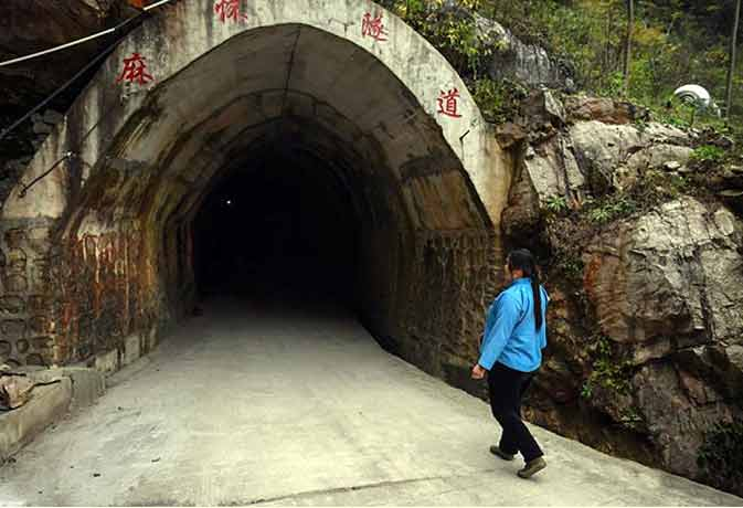woman entering a tunnel she dug next to her village in guizhou