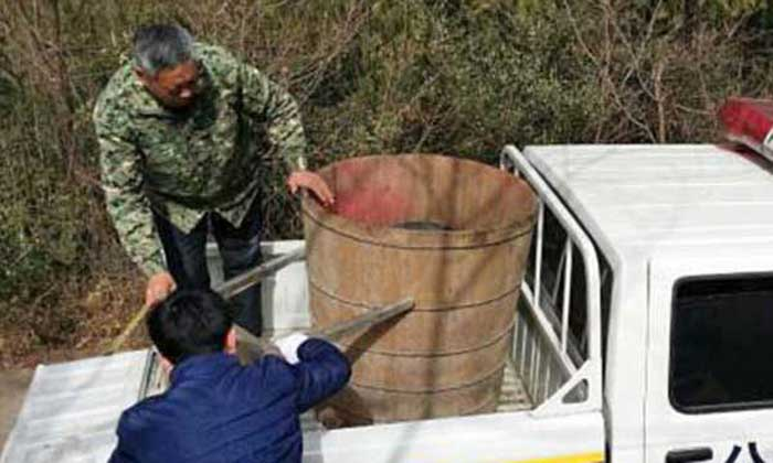 two men loading a barrel onto a police truck