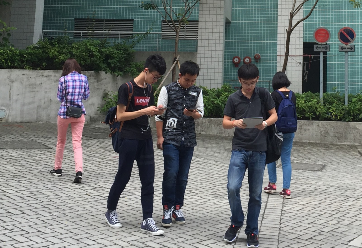 students walking through campus using their mobile phones