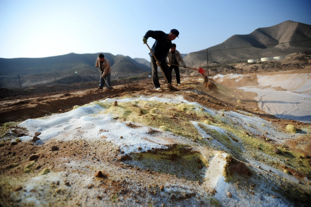 farmers working soil polluted land in china