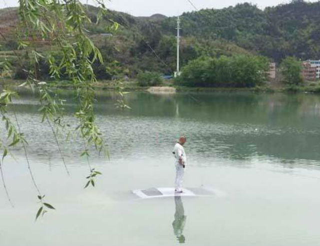 man standing on top of his car in a lake in china