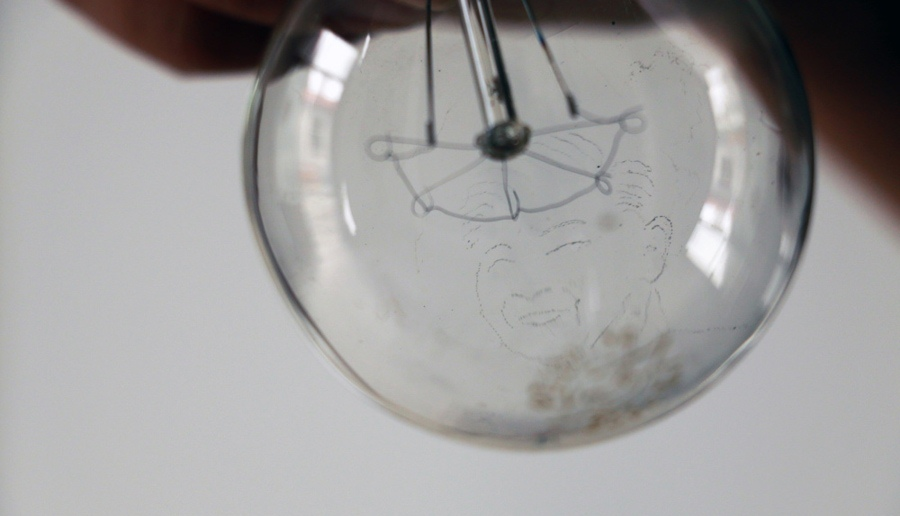close up view of a lightbulb with a hand engraved design in the glass