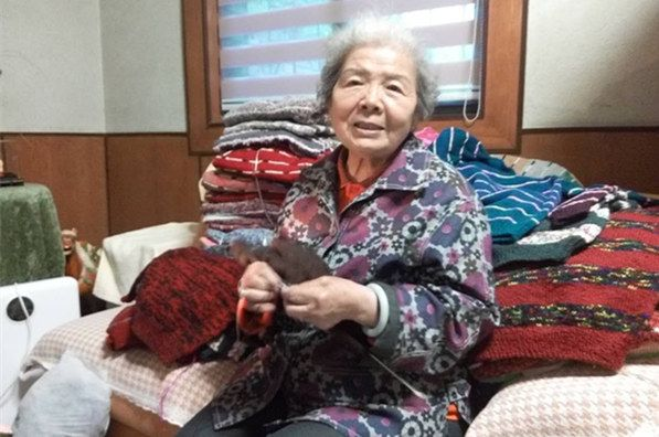 front view of sweater grandma sitting on a bed knitting