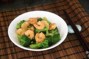 bowl of stir fry king prawn on bamboo placement with chopsticks